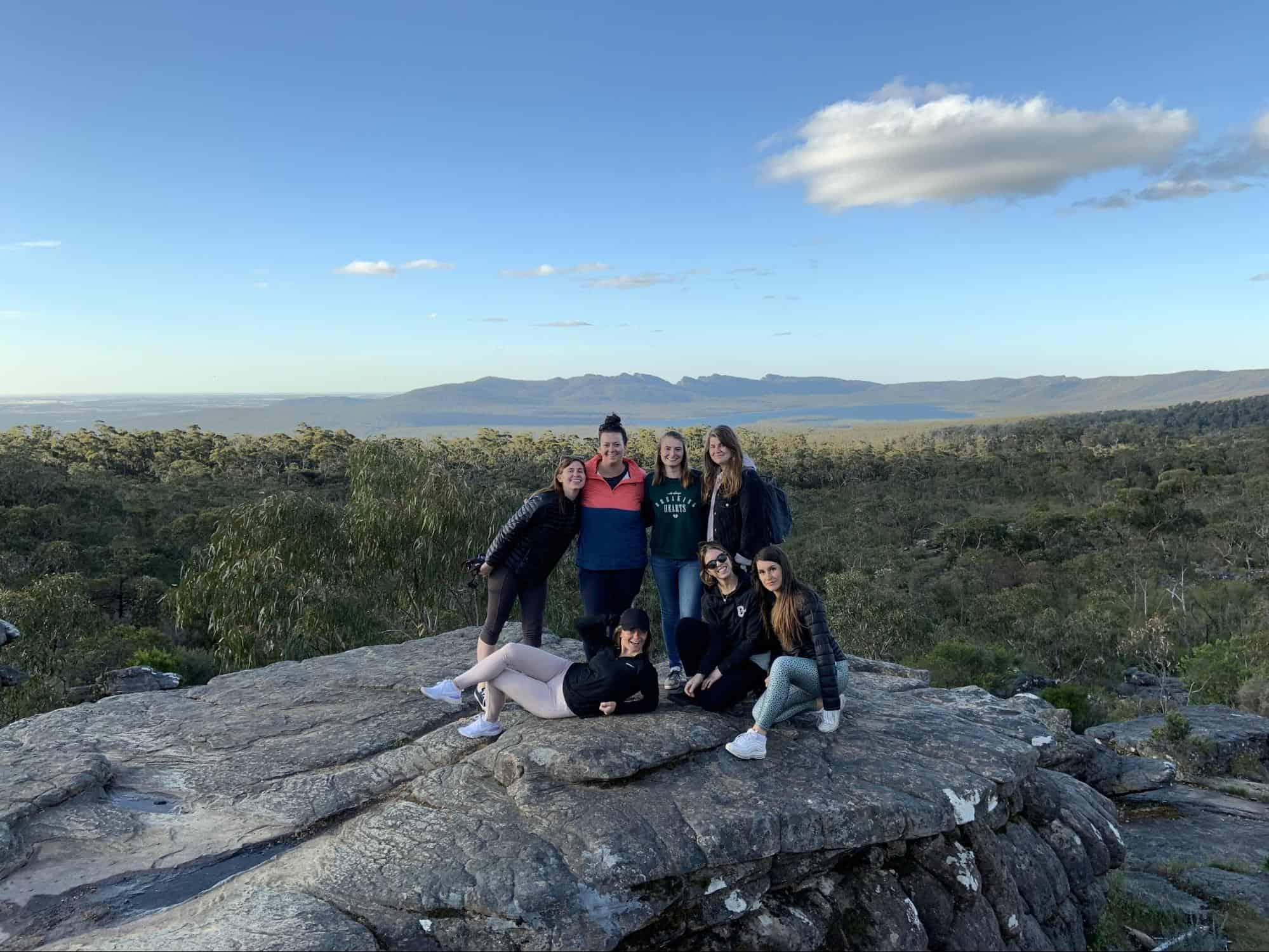 A group of travelling girls pose on a mountain cliff