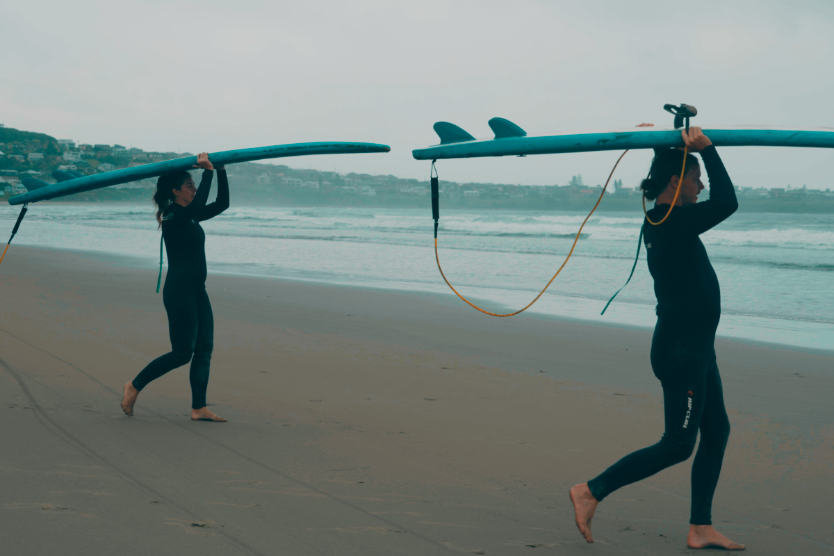 Two people in surf wetsuits carrying surfboards on their heads